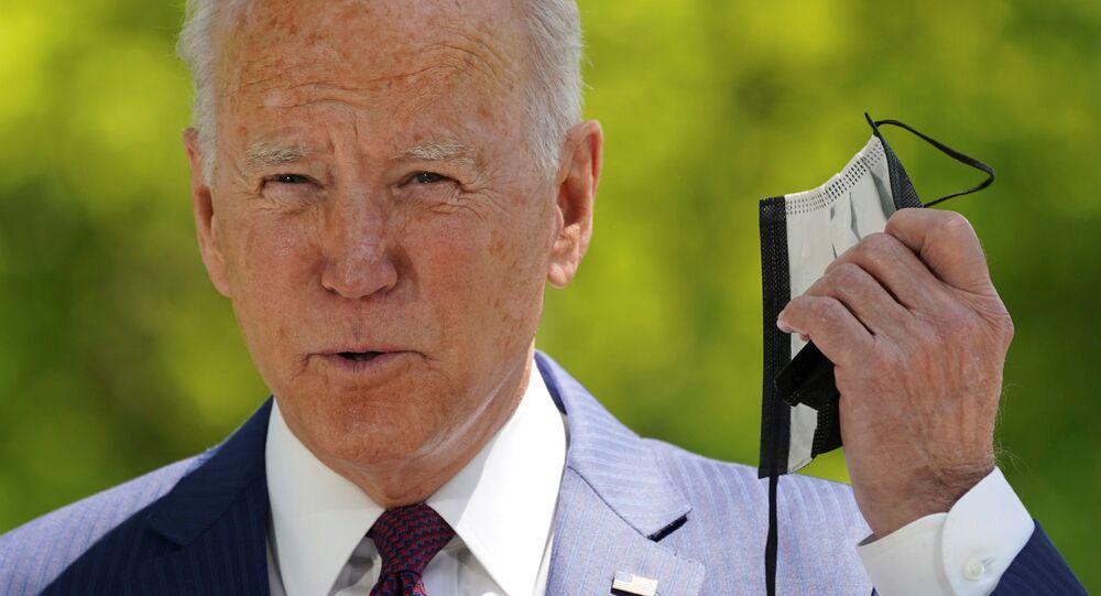 Em Washington, o presidente dos Estados Unidos, Joe Biden, tira a máscara de proteção contra a COVID-19 antes de falar sobre o trabalho de sua administração na pandemia, em 27 de abril de 2021