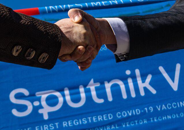 Em Bishek, no Quirguistão, o embaixador da Rússia no país, Nikolai Udovichenko, à esquerda, aperta a mão do vice-primeiro-ministro quirguiz, Artem Novikov, em 22 de abril de 2021