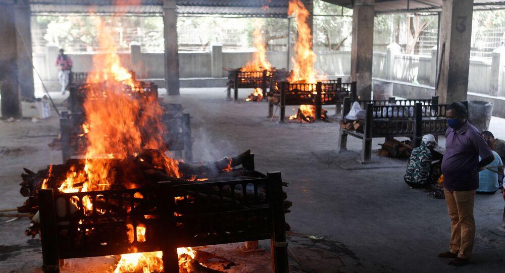 Um parente de um paciente com coronavírus que faleceu depois que um hospital pegou fogo observa enquanto piras funerárias queimam dentro de um crematório em Virar, nos arredores de Mumbai, Índia, 23 de abril de 2021.