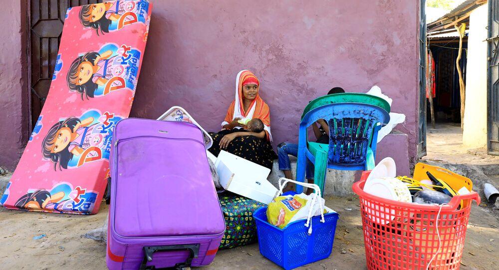 Moradores esperam para fugir após novos confrontos entre facções rivais nas forças de segurança, em Mogadíscio, Somália, 27 de abril de 2021.
