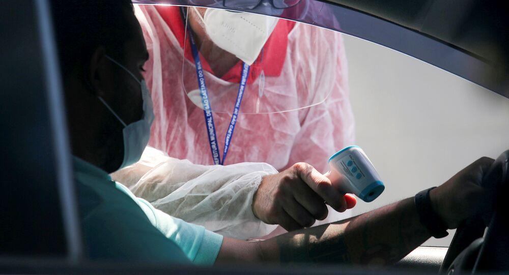 Um trabalhador da área da saúde verifica a temperatura de um homem em uma barreira sanitária, em São Caetano do Sul, no estado de São Paulo, no dia 29 de março de 2021