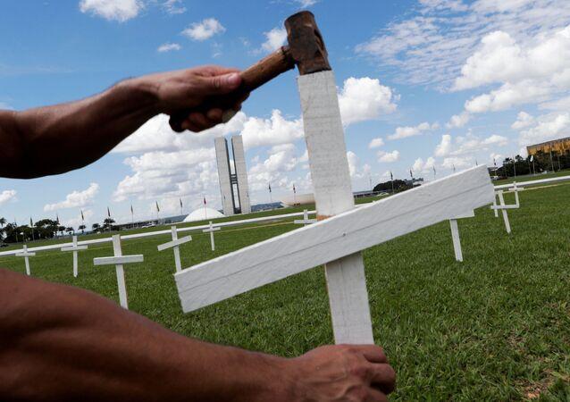 Manifestante coloca cruz na frente do Congresso Nacional, em memória às vítimas da COVID-19, Brasília, 27 de abril de 2021