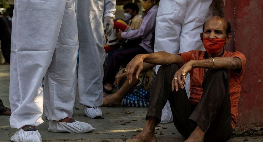 Homem espera para cremar seu parente, que morreu devido à COVID-19, em um crematório em Nova Deli, na Índia