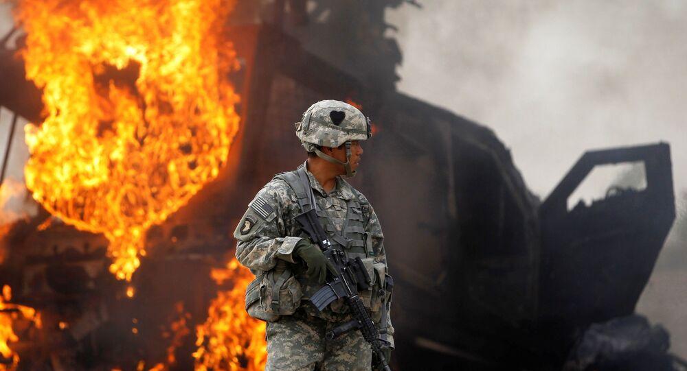 Sodado norte-americano faz monitoramento no Afeganistão enquanto veículo pega fogo ao fundo