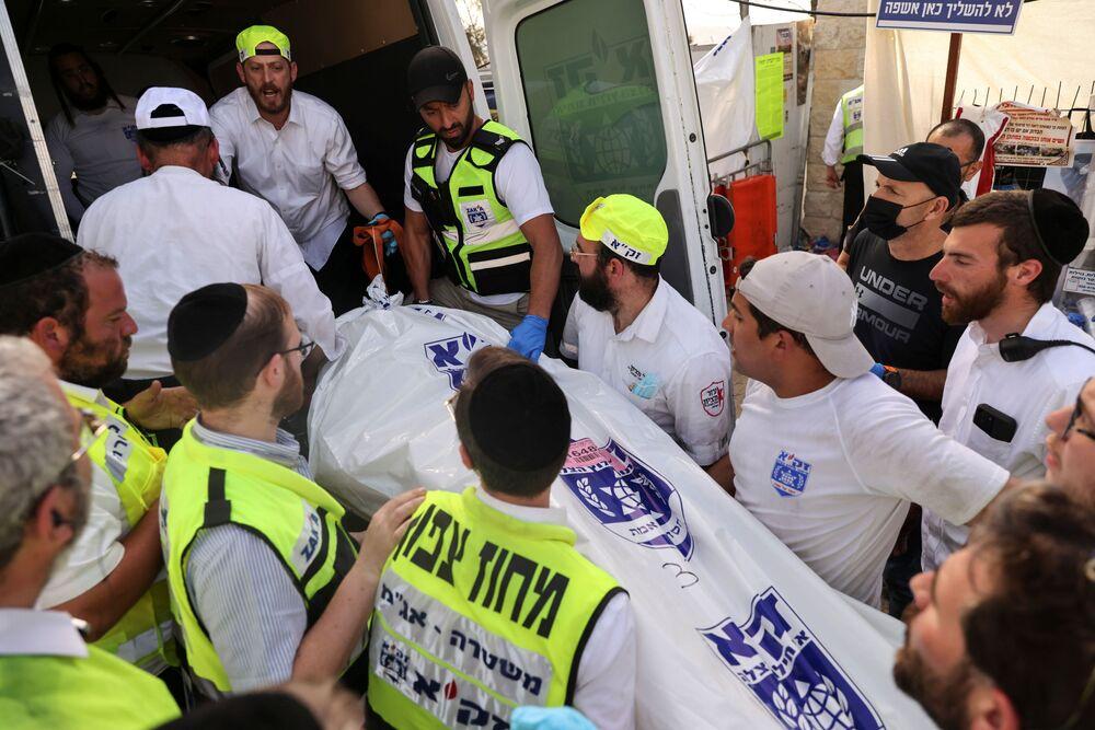 Socorristas colocam o corpo de uma vítima em ambulância na sequência da debandada no monte Meron