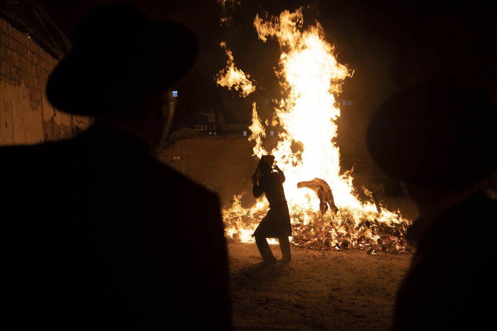 Jovens judeus ultraortodoxos em Jerusalém ao pé de uma fogueira durante o feriado Lag Baômer