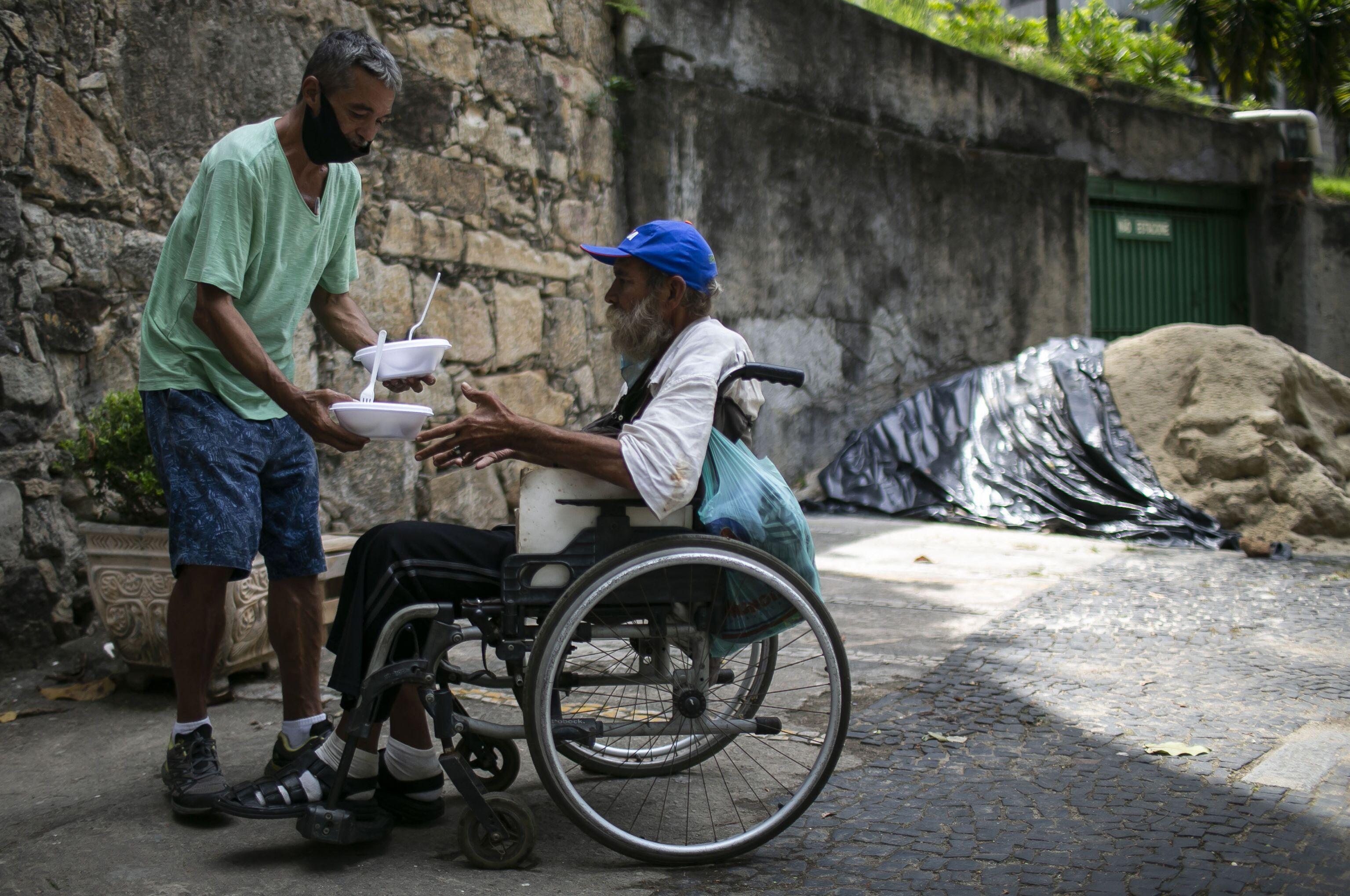Homem doa refeição a cadeirante em convento no Rio de Janeiro, 30 de março de 2021