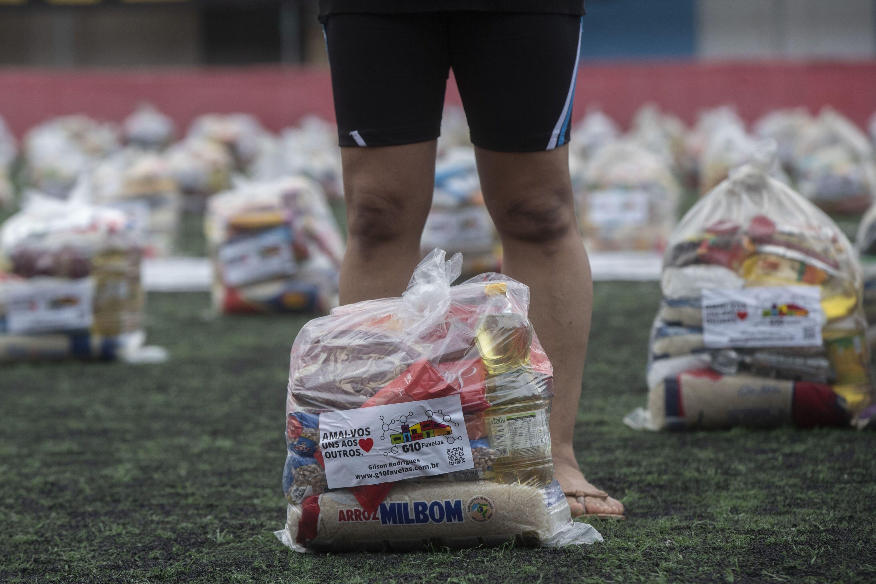 Mulher recebe cesta básica doada pela ONG G10 Favelas, no Capão Redondo, São Paulo, 26 de abril de 2021