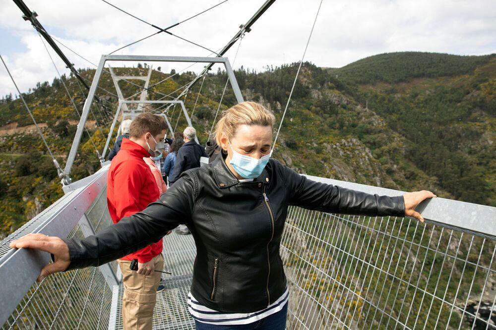 Pessoas se seguram nas laterais da 516 Arouca, ponte suspensa para pedestres, a mais longa do mundo, em Arouca, Portugal, 29 de abril de 2021