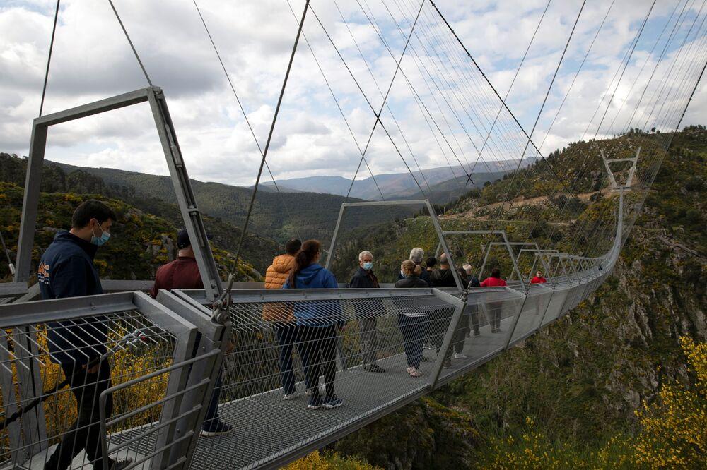 Pessoas caminhando sobre a 516 Arouca, ponte suspensa para pedestres, a mais longa do mundo, em Arouca, Portugal, 29 de abril de 2021