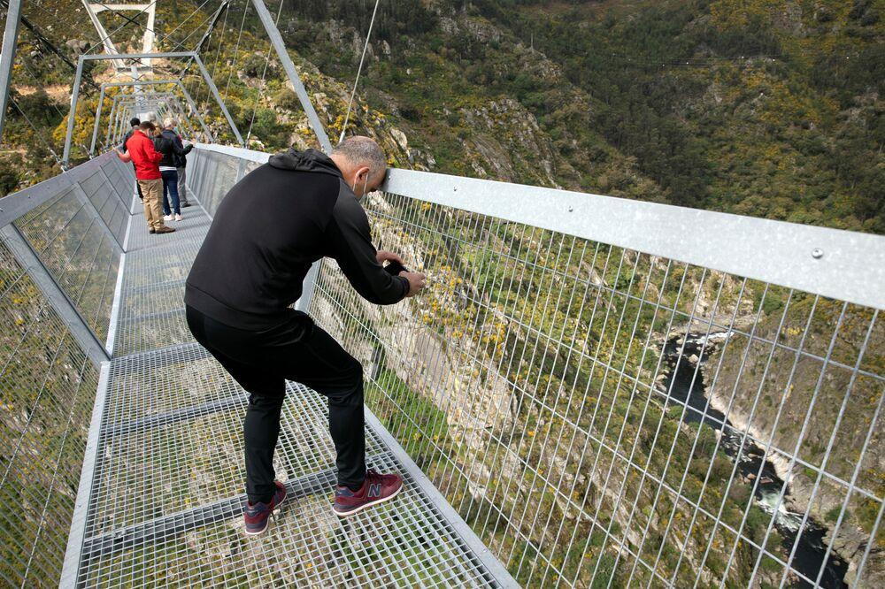 Homem tira foto da paisagem vista entre a grade protetora da 516 Arouca, ponte suspensa para pedestres, a mais longa do mundo, em Arouca, Portugal, 29 de abril de 2021