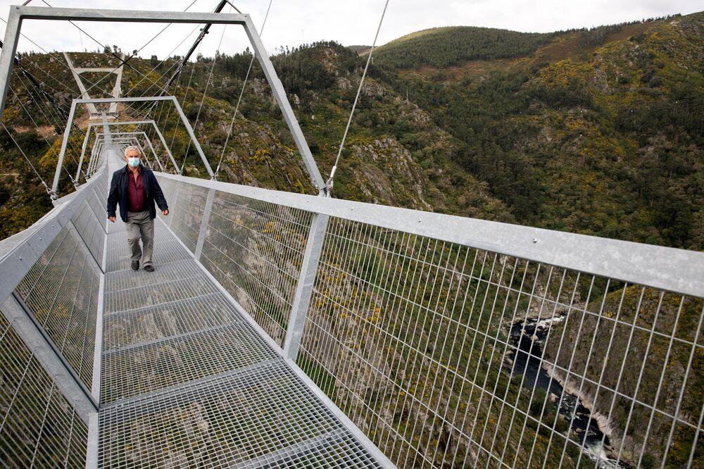 Pessoa caminhando sobre a 516 Arouca, ponte suspensa para pedestres, a mais longa do mundo, em Arouca, Portugal, 29 de abril de 2021