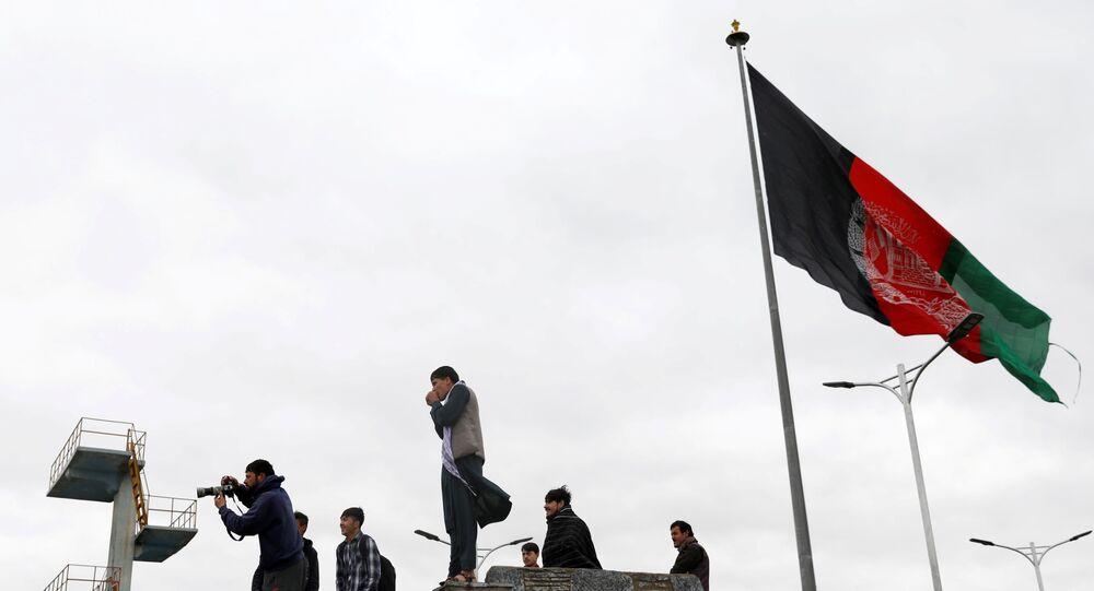 Jovens tiram fotos ao lado de uma bandeira afegã no topo de uma colina com vista para Cabul, Afeganistão, 15 de abril de 2021.