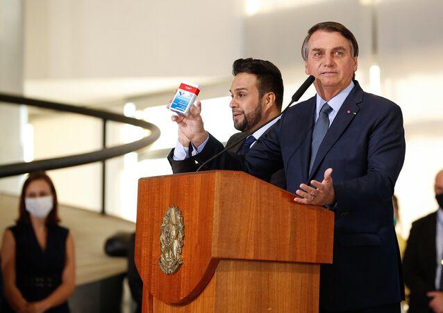 O presidente da República, Jair Bolsonaro, segura cerimônia caixa de hidroxicloroquina no Palácio do Planalto.