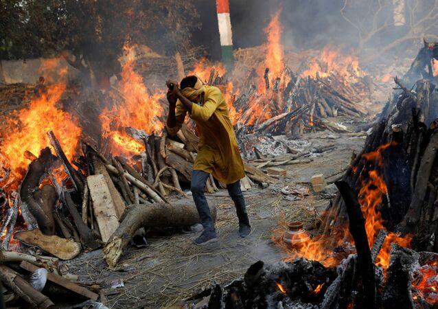 Homem corre ao lado de piras funerárias de mortos da COVID-19 durante cremação em massa em Nova Deli, Índia, 26 de abril de 2021