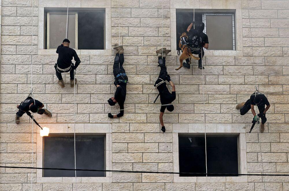 Membros palestinos das forças de segurança do Hamas descem ao longo de uma parede demonstrando sua destreza durante uma cerimônia de graduação de policiais na Cidade de Gaza, 26 de abril de 2021