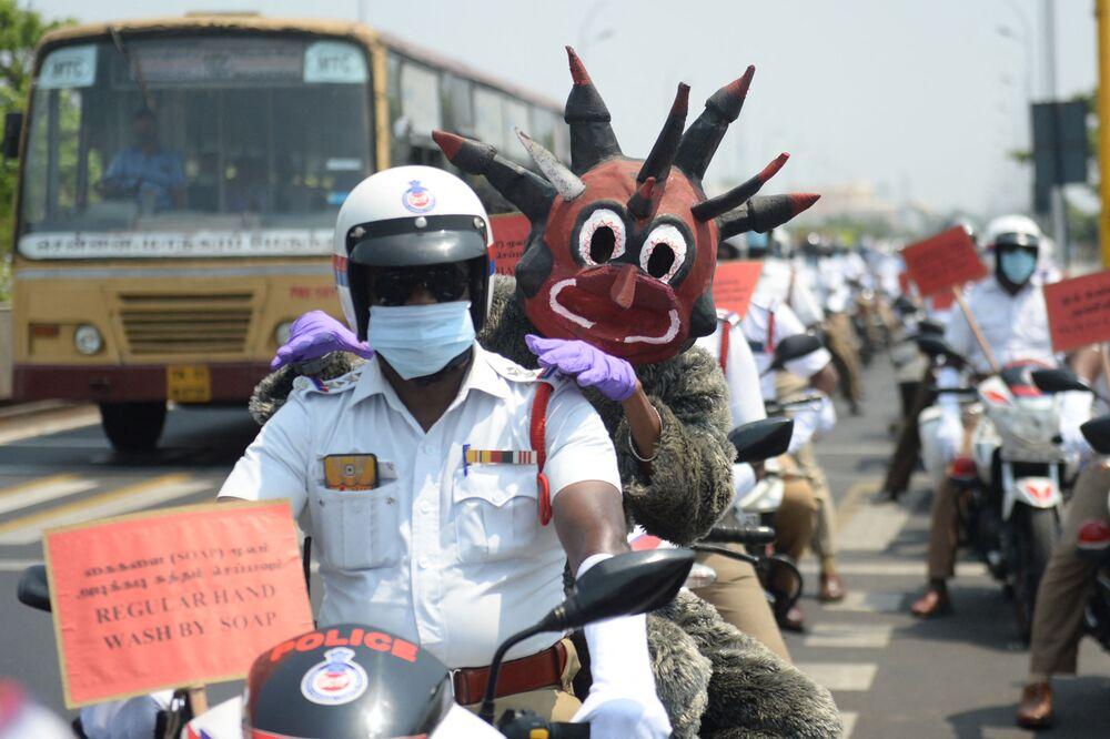 Policial fantasiado de demônio parecido com a COVID-19 participa de manifestação de conscientização sobre o novo coronavírus em Chennai, Índia, 29 de abril de 2021