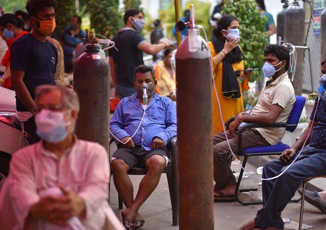 Pessoas que sofrem de dificuldades respiratórias recebem gratuitamente oxigênio no templo de Gurdwara, Deli, Índia