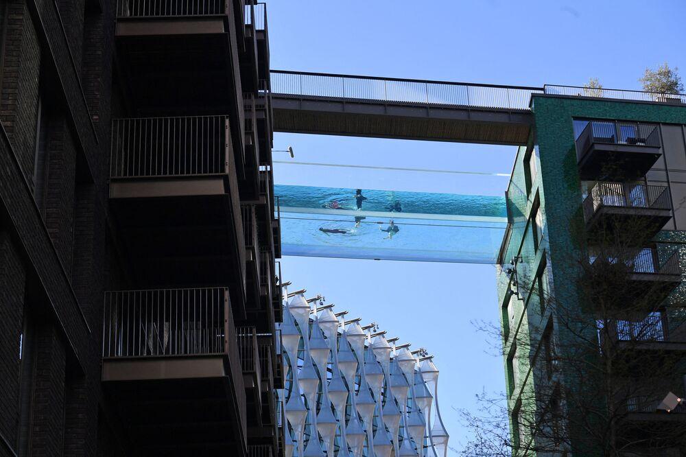 Modelos nadam na primeira piscina transparente aberta de 25 metros chamada de Sky Pool e fixada entre dois prédios de apartamentos, Londres, Reino Unido, 22 de abril de 2021.