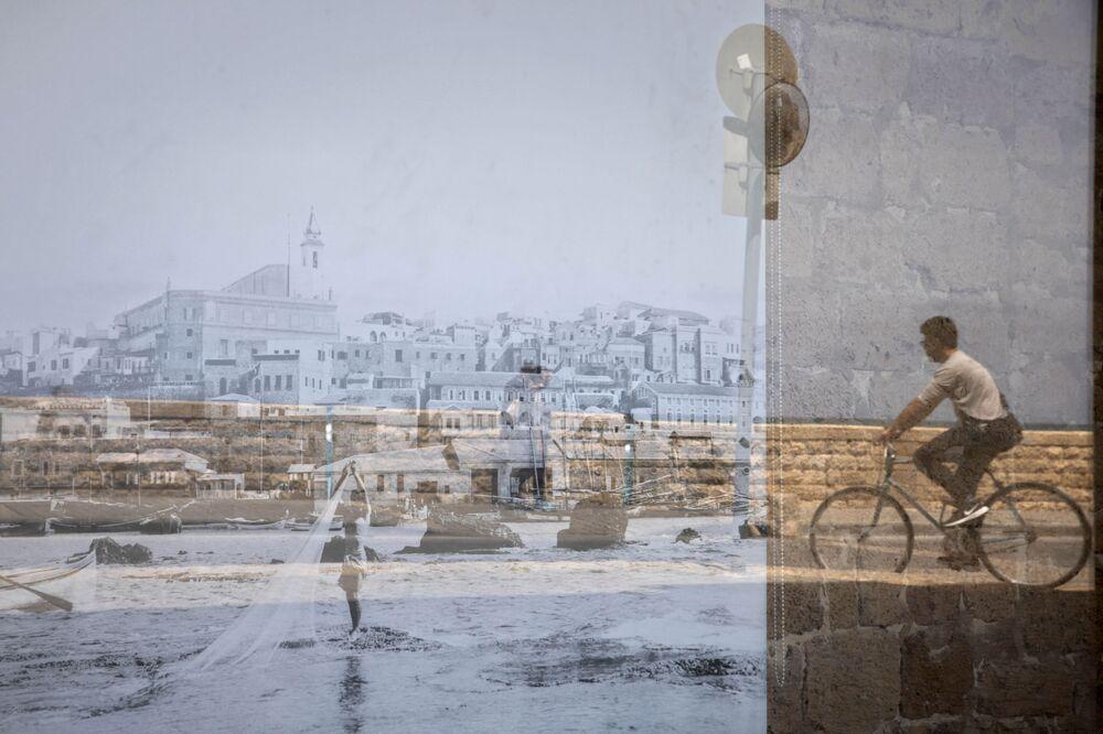 Homem passa de bicicleta sendo refletido em uma foto antiga de Jafa exibida em uma janela, no bairro de Jafa de Tel Aviv, Israel, 21 de abril de 2021