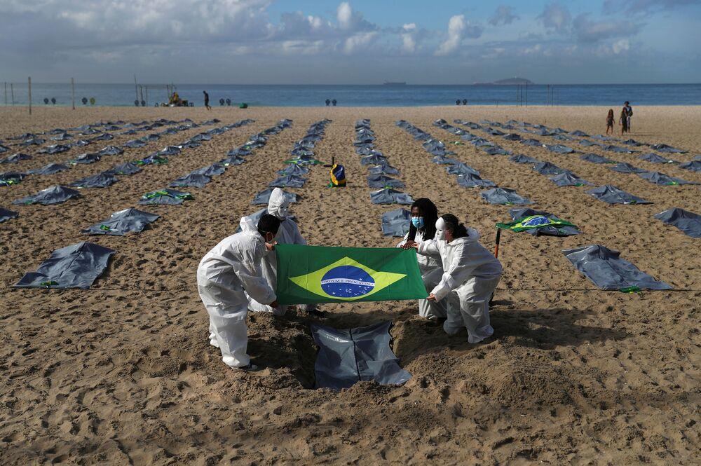 Ativistas da organização não governamental Rio de Paz carregam a bandeira brasileira, enquanto exibem centenas de sacos de plástico representando mortos e relembrando os 400 mil óbitos pela COVID-19, durante protesto contra a política de Jair Bolsonaro para a COVID-19, praia de Copacabana, Rio de Janeiro, Brasil, 30 de abril de 2021