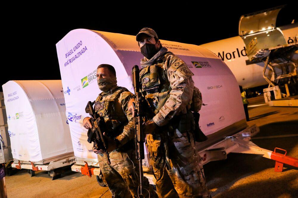 Membros das forças de segurança vigiam perto dos contêineres com doses da vacina da Pfizer/BioNTech no Aeroporto Internacional de Viracopos, Campinas, São Paulo, Brasil, 29 de abril de 2021