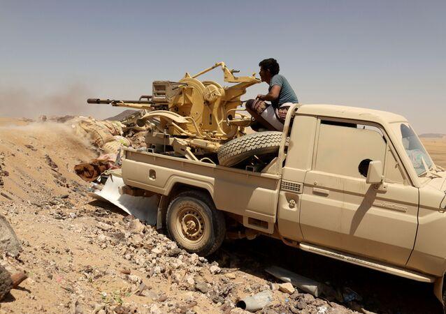 Combatente do governo do Iêmen dispara arma montada em um veículo durante combate contra militantes houthis em Marib, Iêmen, 28 de março de 2021