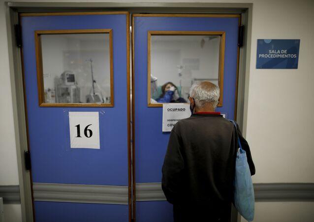 Marido observa sua esposa com suspeita de COVID-19 durante atendimento em hospital da cidade de Lomas de Zamora, Argentina, 1 de maio de 2021