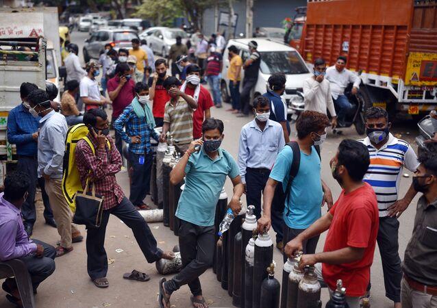 Pessoas esperam ao lado de cilindros de oxigênio do lado de fora de uma estação para reabastecê-los, em meio à disseminação da doença do coronavírus, em Deli, na Índia.