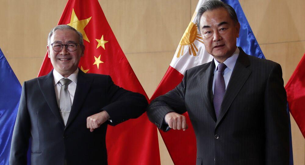 Secretário de Relações Exteriores das Filipinas, Teodoro Locsin (à esquerda), e ministro das Relações Exteriores da China, Wang Yi (à direita)