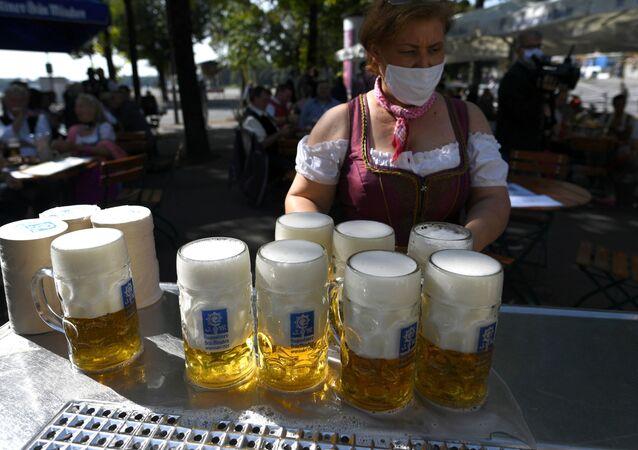 Em Munique, na Alemanha, uma garçonete carrega canecas de cerveja na região onde a Oktoberfest seria realizada se não tivesse sido cancelada devido à pandemia, em 3 de maio de 2021