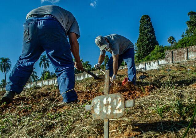 Funcionários de cemitério em Porto Alegre realizam enterro de vítima da COVID-19.