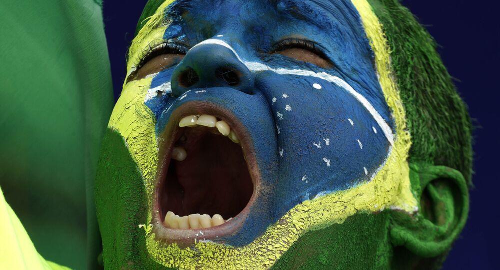 Manifestante pinta o rosto com as cores da bandeira do Brasil durante ato a favor do presidente Jair Bolsonaro, 1 de maio de 2021