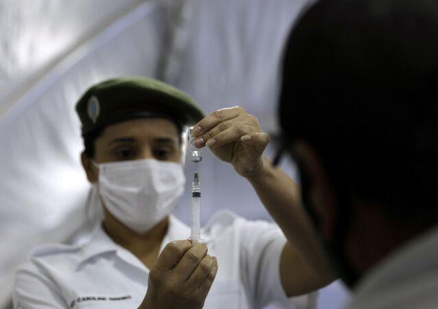 Enfermeira do Exército brasileiro prepara dose de vacina contra a COVID-19 para vacinação de militares, no Rio de Janeiro, 3 de maio de 2021