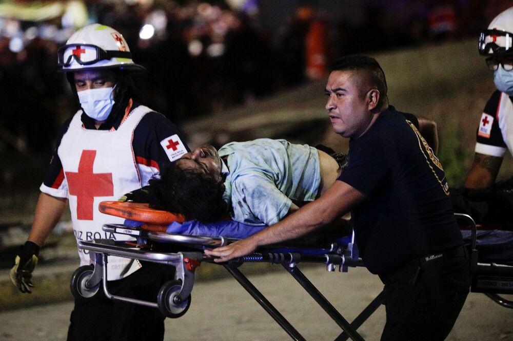 Socorristas transportam uma pessoa ferida em maca no local do desabamento do viaduto do metrô na estação Olivos na Cidade do México, 3 de maio de 2021