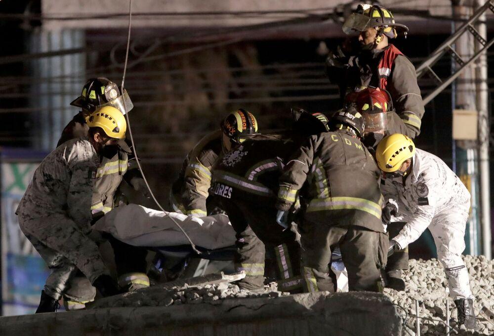 Socorristas carregam um morto no local de desabamento do viaduto do metrô na estação Olivos na Cidade do México, 3 de maio de 2021