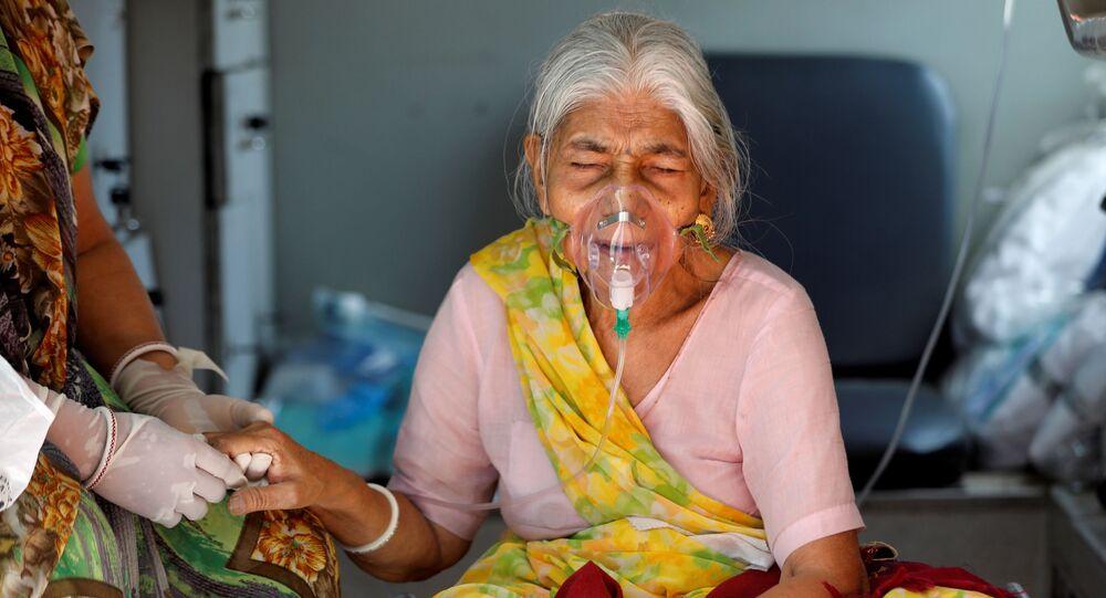 Em Ahmedabad, na Índia, uma mulher idosa com uma máscara de oxigênio é atendida dentro de uma ambulância enquanto aguarda para entrar em um hospital especializado em COVID-19, em 5 de maio de 2021
