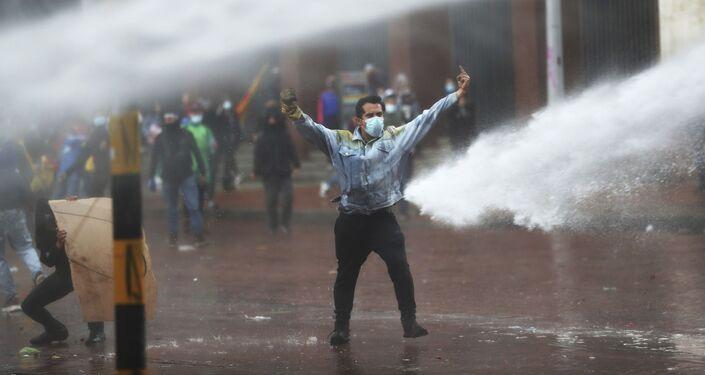 Manifestante faz gesto contra o canhão d'água da polícia durante os protestos antigovernamentais em Bogotá, Colômbia, 5 de maio de 2021
