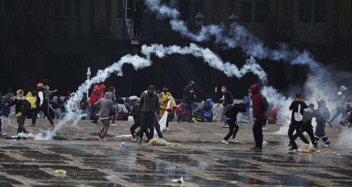 Manifestantes antigovernamentais jogam bombas de gás lacrimogêneo à polícia durante confrontos em Bogotá, Colômbia, 5 de maio de 2021