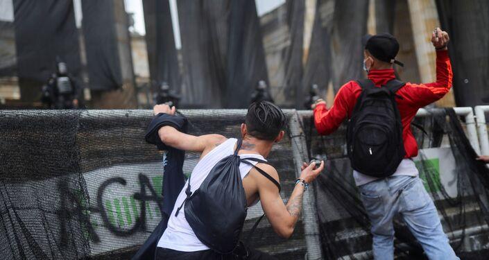 Manifestantes jogam pedras durante os protestos em Bogotá, Colômbia, 5 de maio de 2021