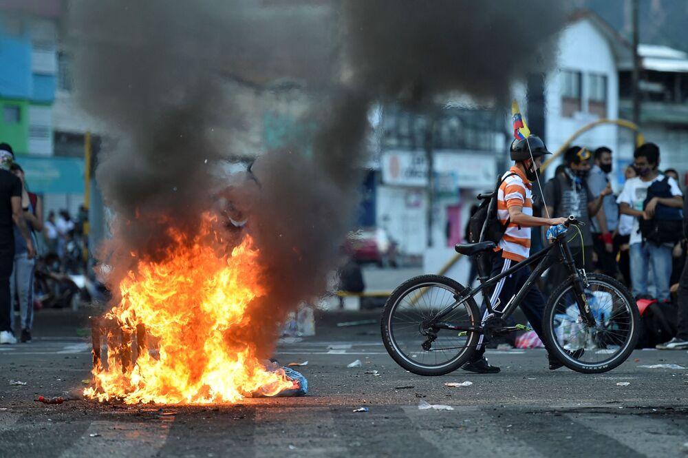 Manifestantes passam por uma barricada em chamas bloqueando a rua durante os protestos contra o governo do presidente Iván Duque em Cali, Colômbia, 5 de maio de 2021