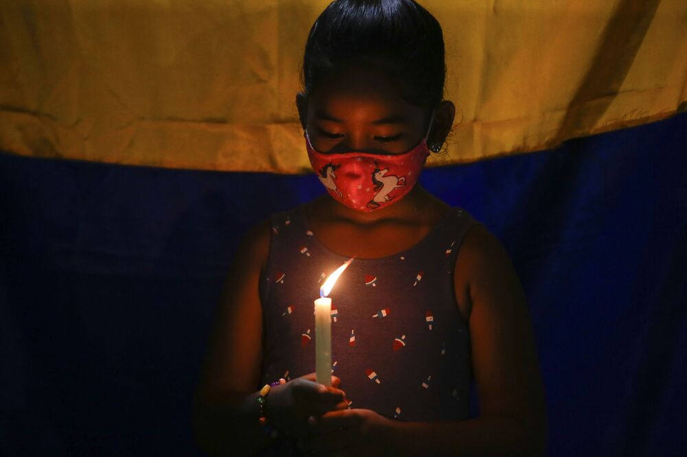 Menina colombiana, moradora no Panamá, segura uma vela durante protestos contra o governo de Iván Duque em apoio às manifestações na Colômbia, Cidade de Panamá, Panamá, 5 de maio de 2021