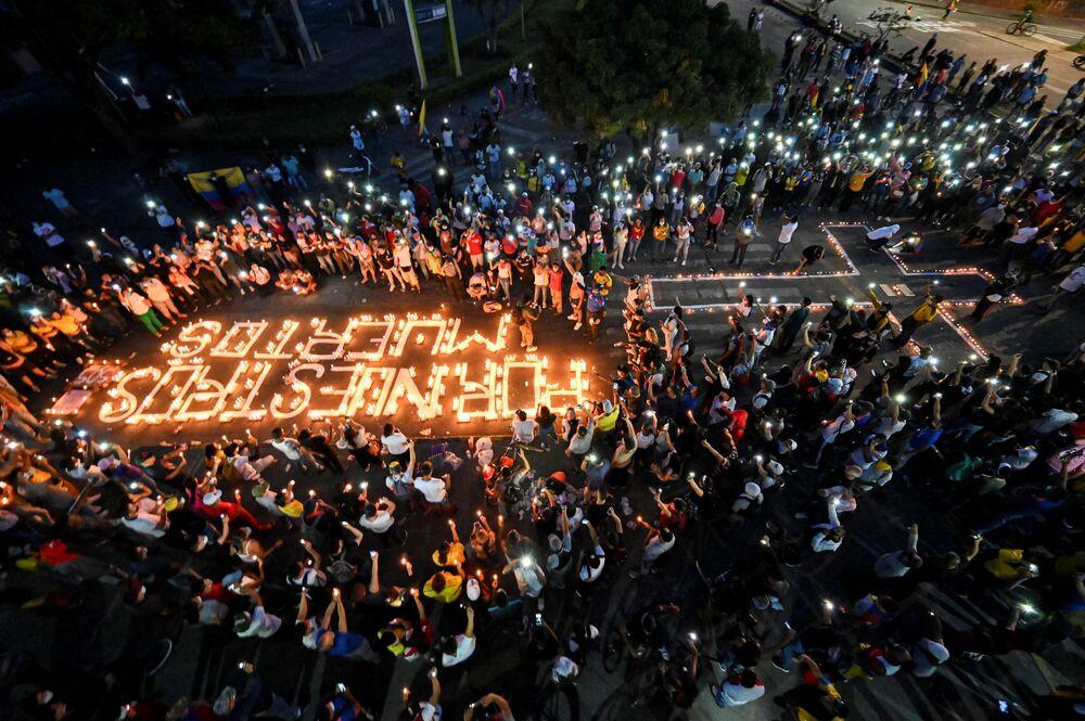 Pessoas se reúnem ao redor de velas e de inscrição na rua por nossos mortos durante vigília em Cali, Colômbia, 5 de maio de 2021