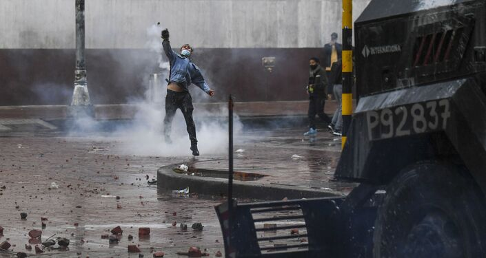 Manifestante joga pedra a um carro policial durante protestos antigovernamentais na praça Bolívar, Bogotá, Colômbia, 5 de maio de 2021