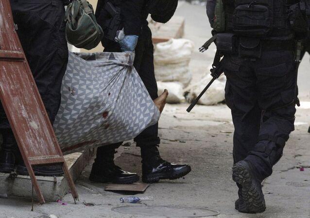 Policiais carregam pessoa durante operação no Jacarezinho, Rio de Janeiro, 6 de maio de 2021