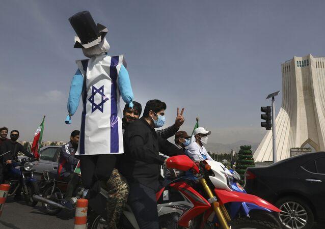 Manifestante em motocicleta ergue uma efígie que representa Israel e os EUA durante o evento anual do Dia de Al-Quds, ou de Jerusalém, 7 de maio de 2021