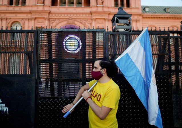 Um manifestante segura uma bandeira argentina em protesto contra as medidas de bloqueio do presidente da Argentina, Alberto Fernandez, em Buenos Aires, em 17 de abril de 2021.