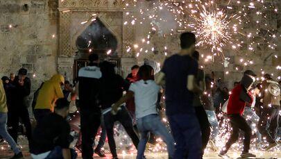 Palestinos reagem ao disparo pela polícia israelense de granadas atordoantes durante confrontos na área da Mesquita Al-Aqsa, conhecida pelos judeus como Monte do Templo, em meio a tensões sobre o possível despejo de famílias palestinas de casas em terras reclamadas pelos colonos judeus no bairro Sheikh Jarrah, na Cidade Velha de Jerusalém, 7 de maio de 2021