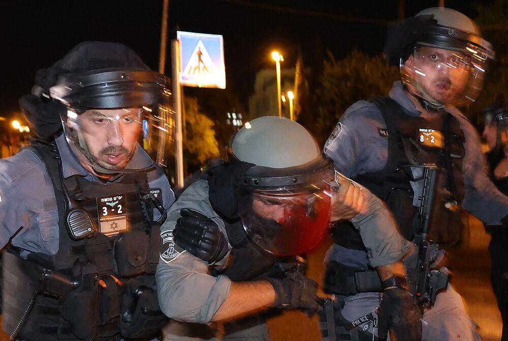 Policial israelense ferido é ajudado durante confrontos com manifestantes palestinos no bairro Sheikh Jarrah em Jerusalém Oriental, 7 de maio de 2021