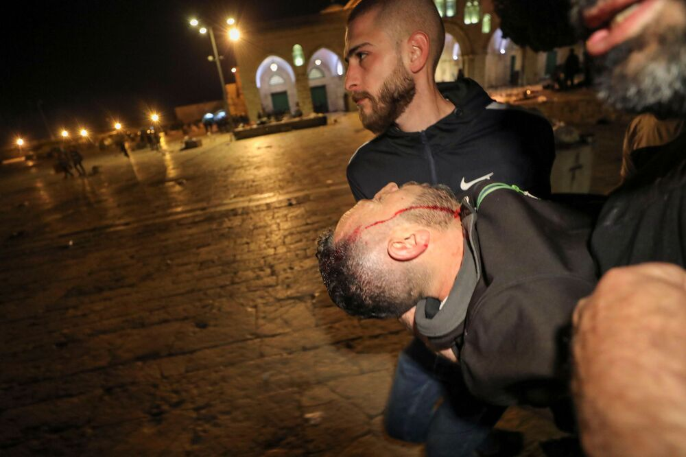 Palestino ferido é evacuado durante confrontos com a polícia israelense na área da Mesquita Al-Aqsa, conhecida pelos muçulmanos como Santuário Nobre e pelos judeus como Monte do Templo, em meio a tensões sobre o possível despejo de famílias palestinas de casas em terras reclamadas pelos colonos judeus no bairro Sheikh Jarrah, na Cidade Velha de Jerusalém, 7 de maio de 2021